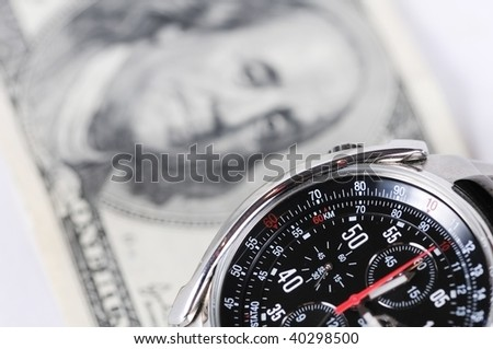 Photo of wrist watch shoot close up against hundred dollars