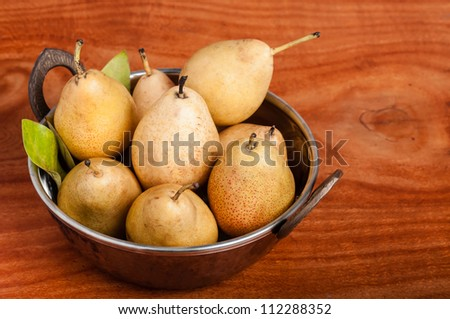 Photo of yellow pears in a copper bowl on a wooden table