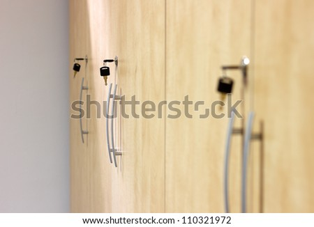 Photo Of Yellow Wooden Closets With Black Keys Plugged In.Small Depth Of  Field