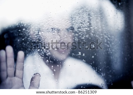 photo of young adult man standing at the window on a rainy day. focus on the raindrops on the glass. toned image