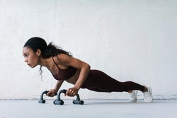 Photo of young african american sportswoman working out with push-up stops indoors