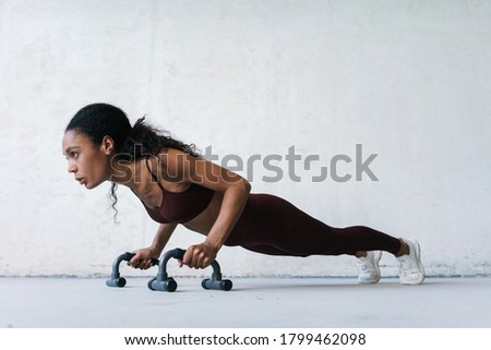 Photo of  Photo of young african american sportswoman working out with push-up stops indoors
