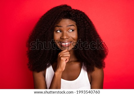 Photo of young african girl happy positive smile hand touch chin think look empty space isolated over red color background