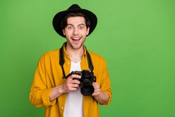 Photo of young amazed excited smiling man photographer take amazing picture isolated on green color background