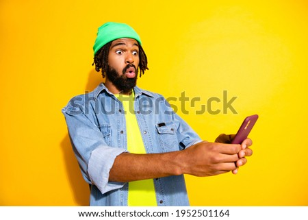 Photo of young amazed surprised man in green beanie see shocking news in cellphone isolated on yellow color background Photo stock ©