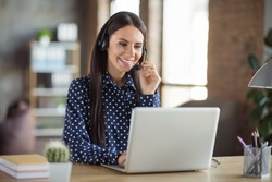 Photo of young attractive beautiful smiling positive businesswoman call operator talking in headphones work in laptop at office