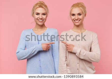 Photo of young broadly smiling happy blonde twins, pointing at each other isolated over pink background.