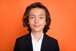 Photo of young brunette calm peaceful boy wear formalwear suit uniform isolated on orange color background