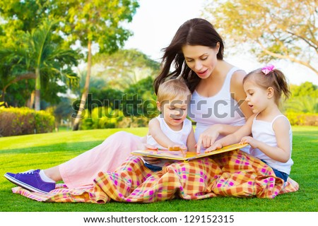 Photo of young brunette woman teaching two sweet kids, cheerful mother with cute daughter and lovely son read interesting fairytale, children enjoying book on backyard in daycare, spring season