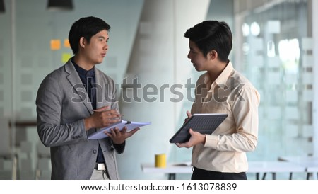 Photo of young business consulting man while talking/giving an advice to customer.
