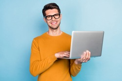 Photo of young business man happy positive smile use laptop work programmer isolated over blue color background