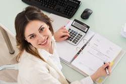 Photo Of Young Businesswoman Calculating Invoice In Office
