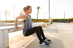 Photo of young caucasian girl in sportswear squatting, and doing workout using concrete bench in sport park at sunrise