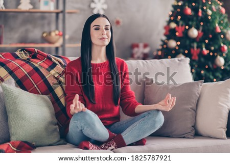 Photo of young charming woman sit couch lotus pose eyes closed wear red pullover jeans socks in decorated living room home indoors