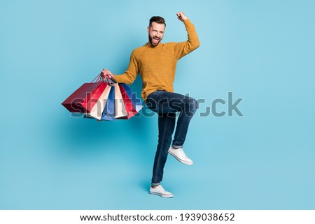 Photo of young cheerful excited crazy positive man hold shopping bags raise fist in victory isolated on blue color background