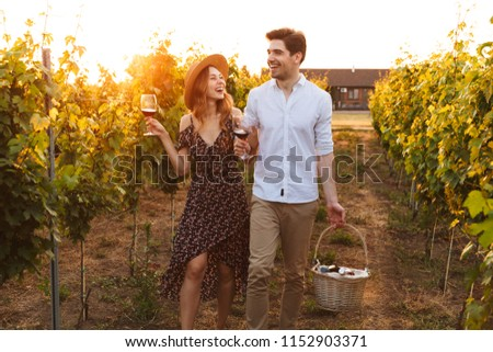 Photo of young cute happy loving couple outdoors drinking wine holding basket with bottles.