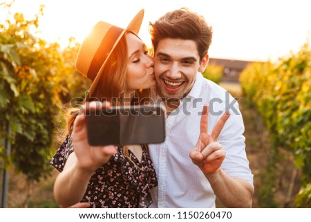 Photo of young cute happy loving couple outdoors take a selfie by mobile phone.