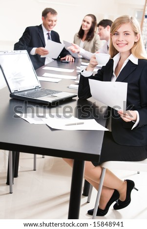 Photo of young employee sitting at table with laptop on it while holding paper and cup of coffee in hands