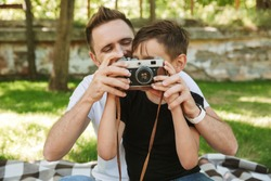 Photo of young father sitting with his little son outdoors in park nature holding camera photographing.