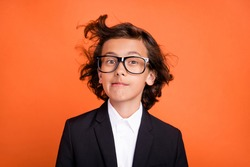 Photo of young funny funky happy boy wind blow hair wear formalwear suit isolated on orange color background