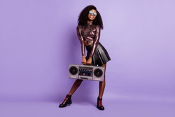 Photo of young girl hold boom box wear vintage glasses glossy shirt mini skirt isolated violet color background