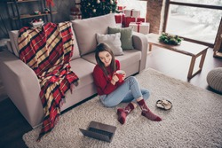 Photo of young girl sit carpet couch look screen netbook hold mug wear red sweater socks jeans in decorated x-mas living room indoors