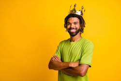 Photo of young handsome african man folded arms happy positive smile wear crown isolated over yellow color background