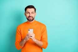 Photo of young handsome man happy positive smile use smartphone dream look empty space isolated over teal color background