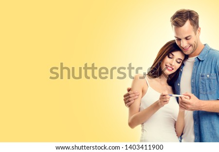 Photo of young happy excited couple, finding out results of a pregnancy test, over yellow color background. Caucasian models - in love, relationship, planning of maternity concept picture.