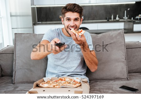 Photo of young happy man holding remote control and pushing the button while eating pizza.