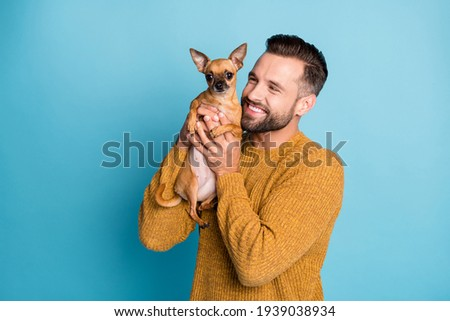 Photo of young happy positive smiling handsome man holding doggy chiahuahua isolated on blue color background