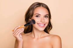 Photo of young happy smiling beautiful woman doing contouring apply blush on cheeks isolated on beige color background