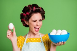 Photo of young housewife hold bowl eggs isolated green color background