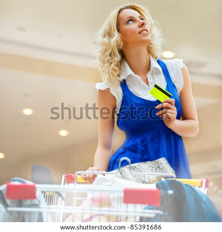 Photo of young joyful woman with shopping bags inside mall driving her trolley full of clothes, bags, shoes and other purchases