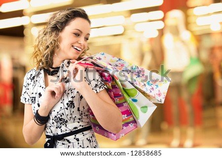 Photo of young joyful woman with shopping bags on the background of shop windows