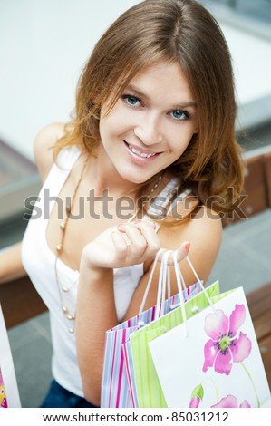 Photo of young joyful woman with shopping bags on the background of shop windows inside shopping mall