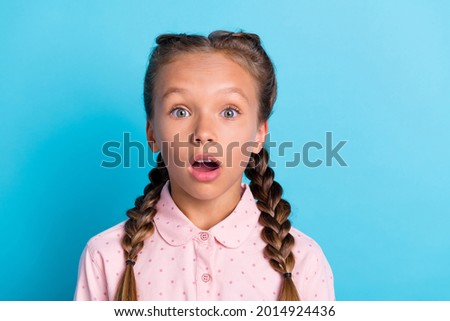 Photo of young little girl amazed shocked surprised stupor fake novelty news isolated over blue color background Foto d'archivio ©