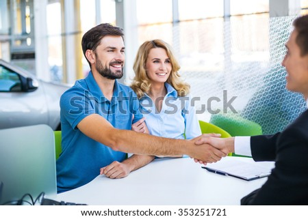 Photo of young male consultant and couple. Young woman and man buying new car in auto show. Signing of contract and shaking hands. Concept for car rental