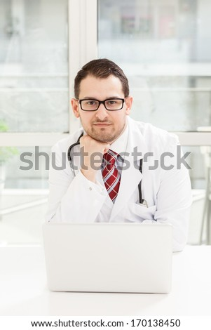 Photo of young male doctor with notebook in his studio