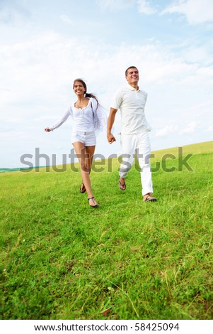 Photo of young man and woman running down bright green grass on summer