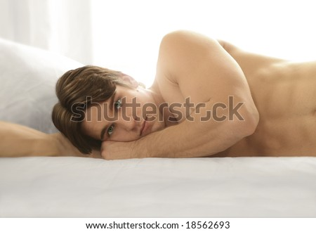 stock photo photo of young man naked in bed and light behind 18562693 gay boy video. MORE AT HELIX STUDIOS