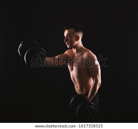 Photo of young man working at his biceps with dumbbells
