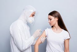 Photo of young patient lady guy expert doc virology inject hand shoulder covid antidote experimental vaccine wear mask hood uniform plastic facial protection isolated grey color background