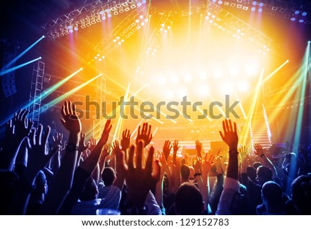 Photo of young people having fun at rock concert, active lifestyle, fans applauding to famous music band, nightlife, DJ on the stage in the club, crowd dancing on dance-floor, night performance #129152783
