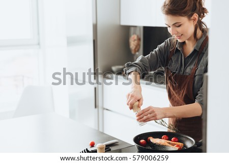 Photo of young pretty lady standing in kitchen while cooking fish. Looking aside. #579006259