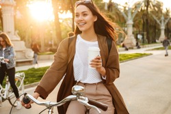Photo of young pretty woman outdoors walking on bicycle on the street in park holding coffee in hand.