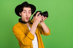 Photo of young shocked amazed cameraman take picture shooting good picture isolated on green color background