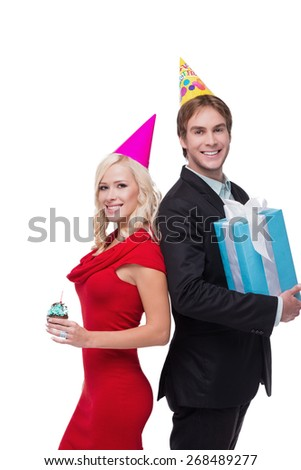 Photo of young smiling man and woman looking at camera with cupcake and present. They wearing birthday hat and standing on white background. Concept for happy birthday