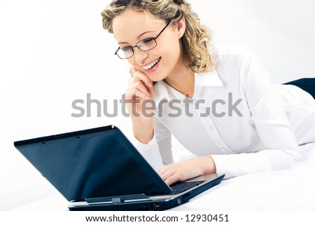 Photo of young smiling woman typing on laptop and looking at its monitor