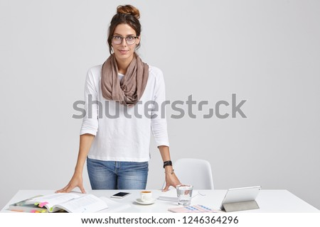 Photo of young teacher in stylish outfit, prepares for seminar or lesson, studies different literary sources, drinks latte, uses tablet for searching information in internet, isolated over white wall